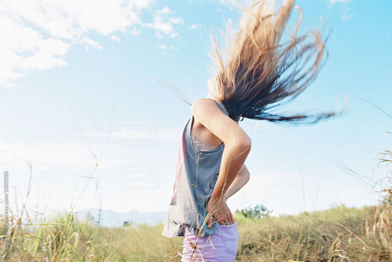 hair flying in blue sky with teen girl being happy by wendy laurel for Stocksy United