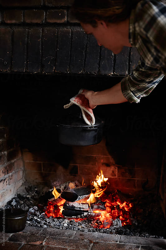 Man cooking pasta on the hearth fire inside his home by Trinette Reed for Stocksy United