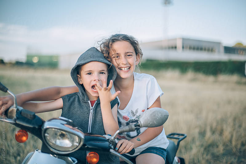 A kids uploaded on the motorcycle in the countryside by Lydia Cazorla for Stocksy United