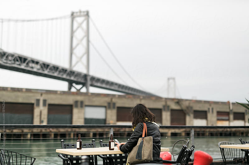 Young woman sitting at table outside in San Francisco by Matthew Spaulding for Stocksy United