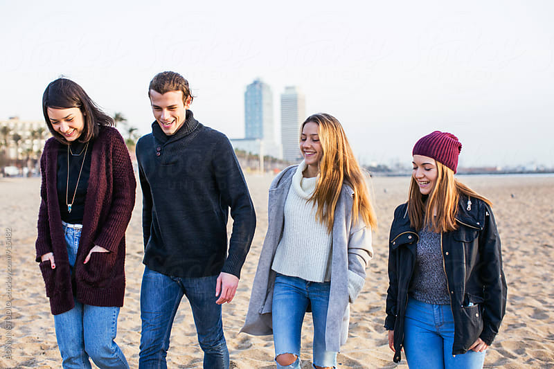Teenage friends walking on the beach at morning. by BONNINSTUDIO for Stocksy United
