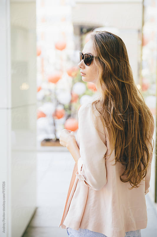 Back view of young woman in sunglasses walking down the street by Andrey Pavlov for Stocksy United