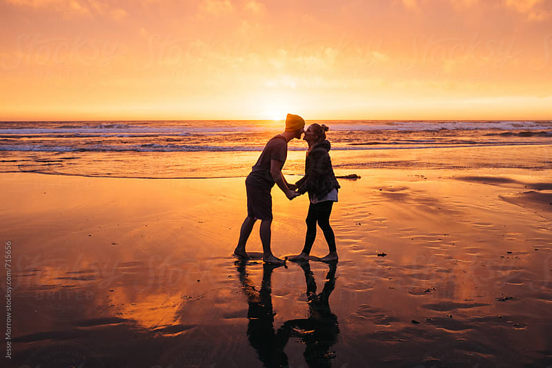 couple in love on the beach kissing and holding hands during sunset by Jesse Morrow for Stocksy United