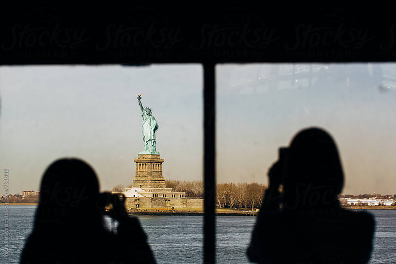 People photographing the Statue of Liberty from the ferry by michela ravasio for Stocksy United