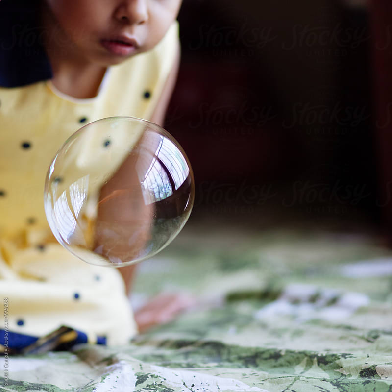 Little girl playing with a big soap bubble by Saptak Ganguly for Stocksy United