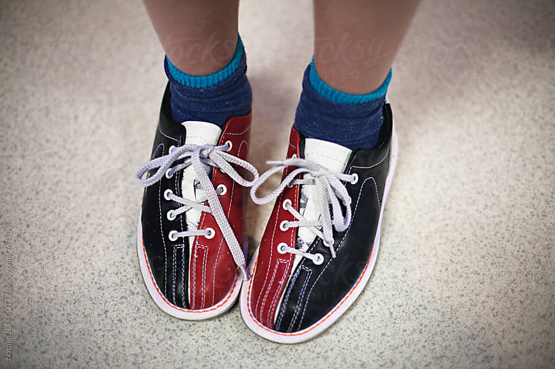 Close up of child's feet wearing bowling shoes by Natalie JEFFCOTT for Stocksy United