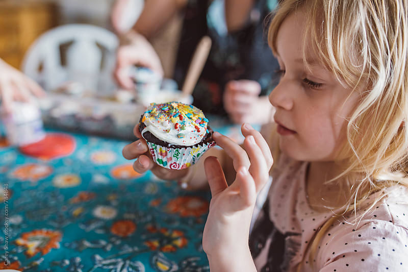 Young girl looking at colorful cupcake by Carey Shaw for Stocksy United