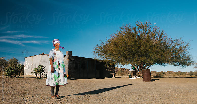 Namibian Nama woman standing outside her home by Micky Wiswedel for Stocksy United