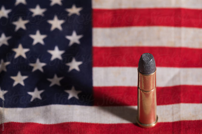 Single bullet on an old grungy US flag by David Smart for Stocksy United