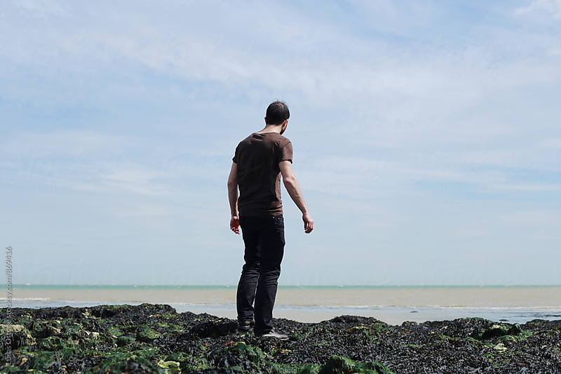 Man standing watching the sea by Lucas Ottone for Stocksy United