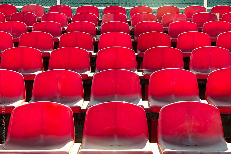 red empty stadium seats by Sonja Lekovic for Stocksy United