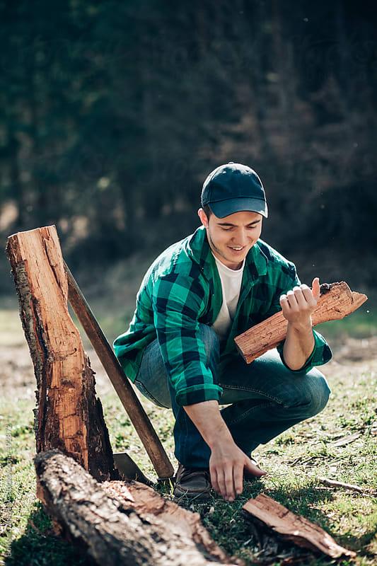 Logger collects chopped wood by Borislav Zhuykov for Stocksy United