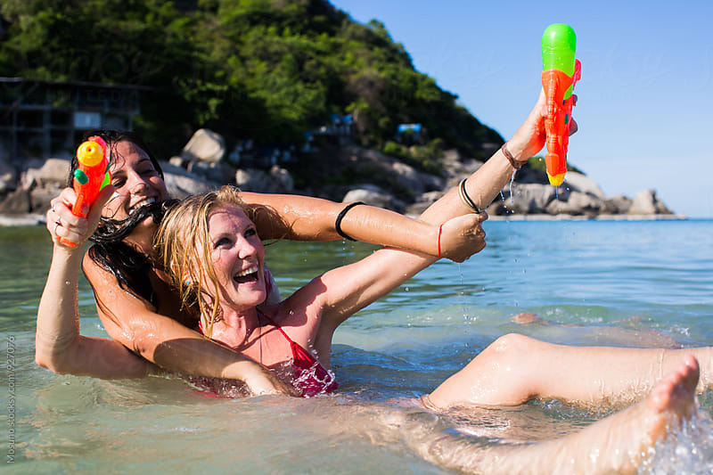 Friends Have a Fun With Water Guns at the Beach by Mosuno for Stocksy United