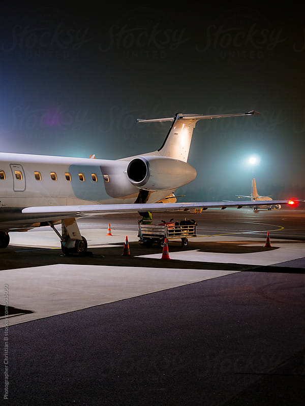 Jet plane on the runway at night by Photographer Christian B for Stocksy United