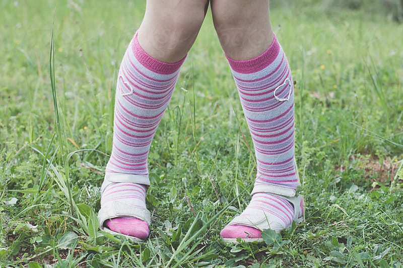 Pink socks with a heart shape paint on them by Beatrix Boros for Stocksy United