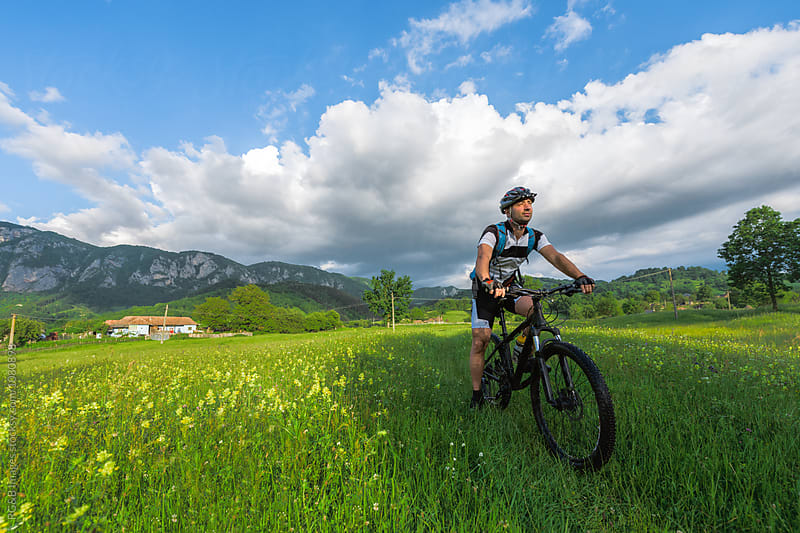 Man sitting on mountain bike in the nature by RG&B Images for Stocksy United