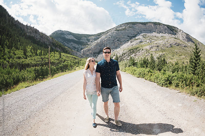 A young couple walking on a gravel path in the mountains by Ania Boniecka for Stocksy United