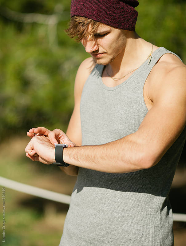 Man in workout session with smartwatch by Leandro Crespi for Stocksy United