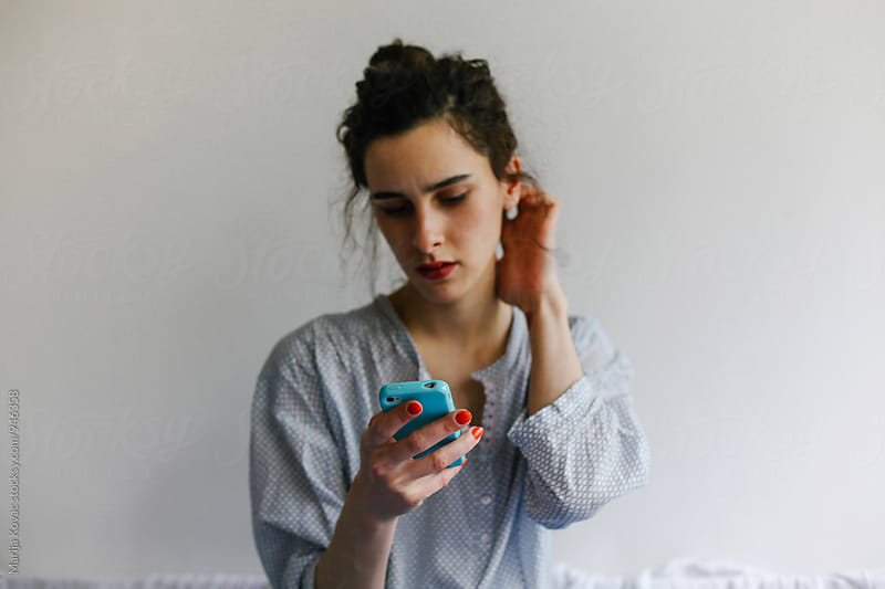 Brunette woman looking at her cell phone by Marija Kovac for Stocksy United