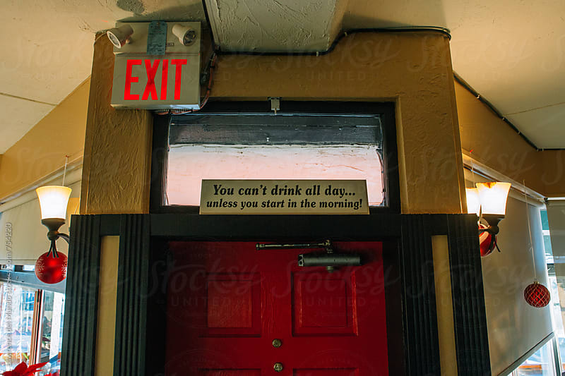 Humorous quote on top of a bar door by Lawrence del Mundo for Stocksy United