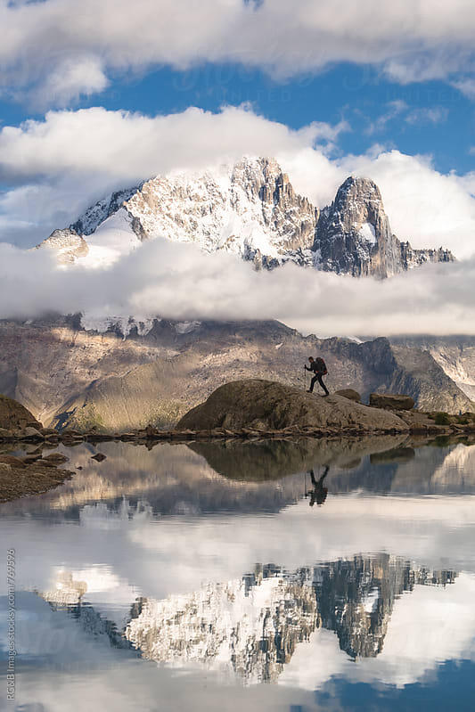 Landscape of mountains and man silhouette  reflecting in the lake by RG&B Images for Stocksy United