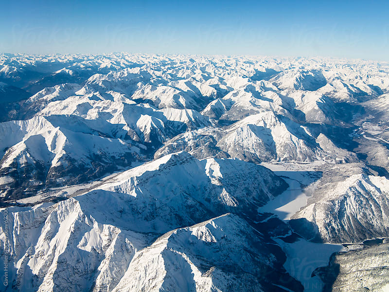 Flying over the snow covered European Alps by Gavin Hellier for Stocksy United
