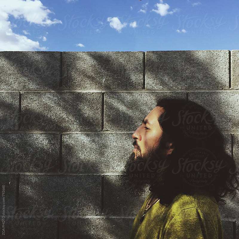 Profile of a man in front of a brick wall by ZOA PHOTO for Stocksy United