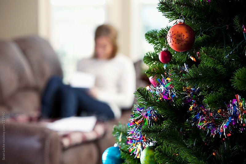 Christmas: Tree with Woman On Couch Behind by Sean Locke for Stocksy United