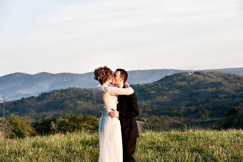 Portrait of a young wedding couple kissing in the Tuscany hills at sunset by Jean-Claude Manfredi for Stocksy United