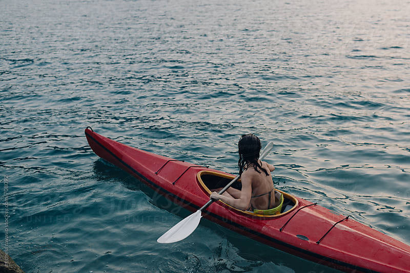 Girl enjoy the lake at sunset in a canoe by michela ravasio for Stocksy United