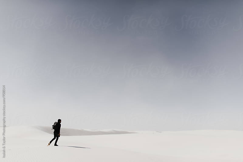 Man walking alone in desert by Isaiah & Taylor Photography for Stocksy United