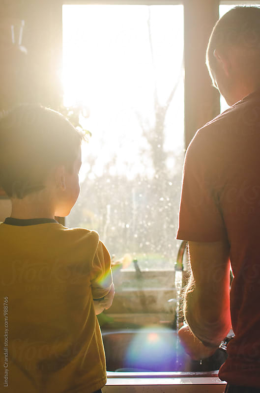 Father working at kitchen sink with young son beside him by Lindsay Crandall for Stocksy United