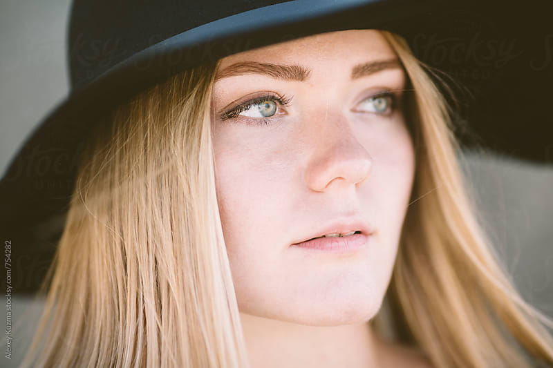 blond woman with black hat  by Alexey Klementiev for Stocksy United