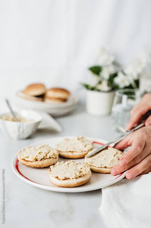 Making vegan sandwiches with hummus by Tatjana Zlatkovic for Stocksy United