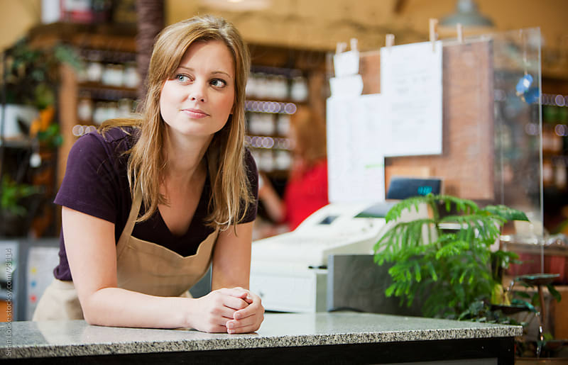 Market: Cashier Daydreaming While At Work by Sean Locke for Stocksy United