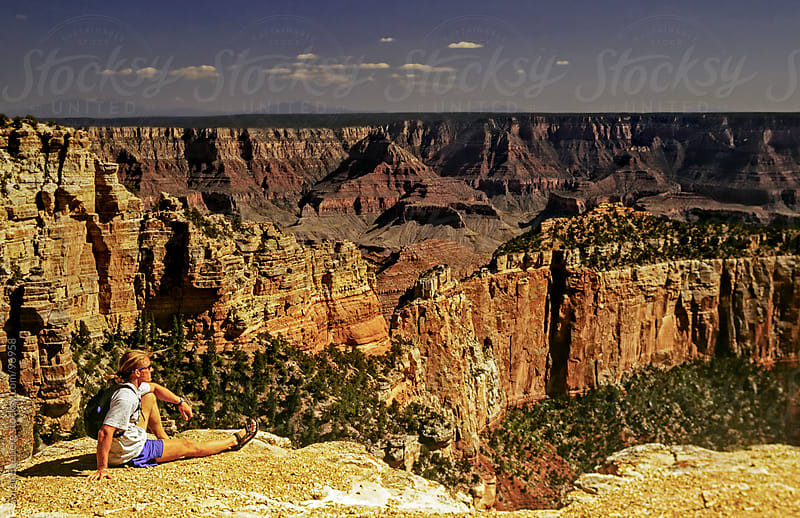 Hiker enjoying view from rocky outcrop in Grand Canyon north rim by Soren Egeberg for Stocksy United