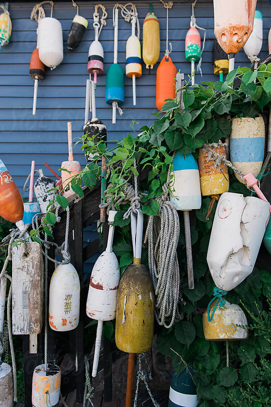 Old lobster trap buoys hanging on a building in Maine by Cara Slifka for Stocksy United