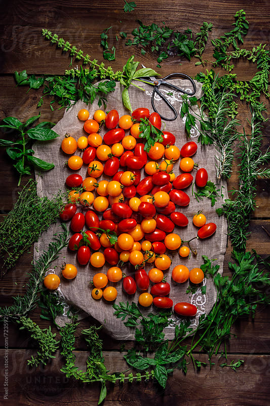 Various cherry tomatoes on wooden table by Pixel Stories for Stocksy United