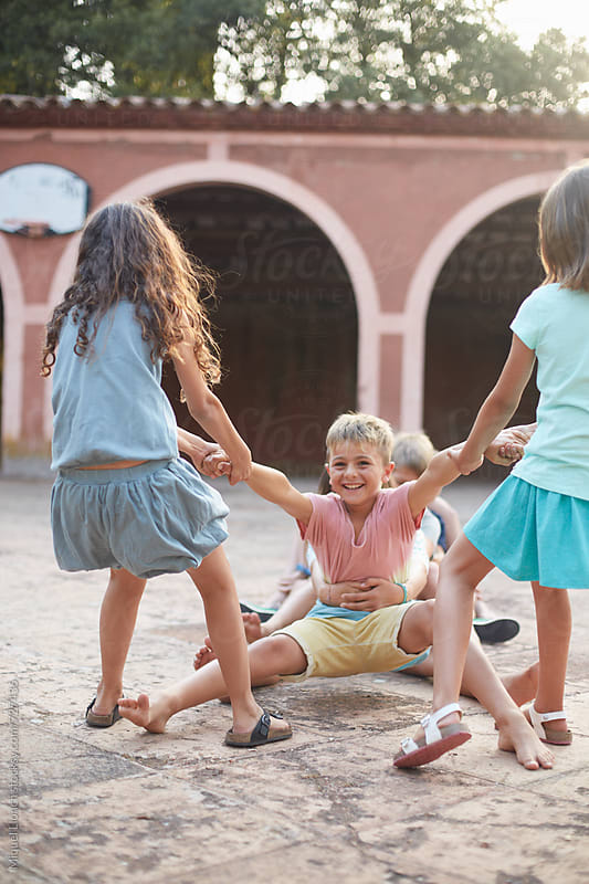 Group of children playing happy and action games by Miquel Llonch for Stocksy United