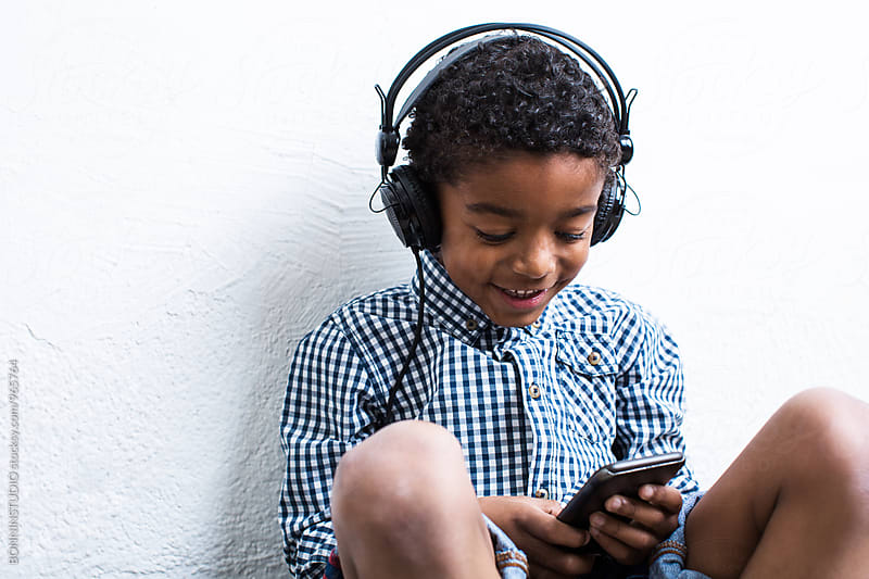 Little boy listening music whilst using smartphone.  by BONNINSTUDIO for Stocksy United