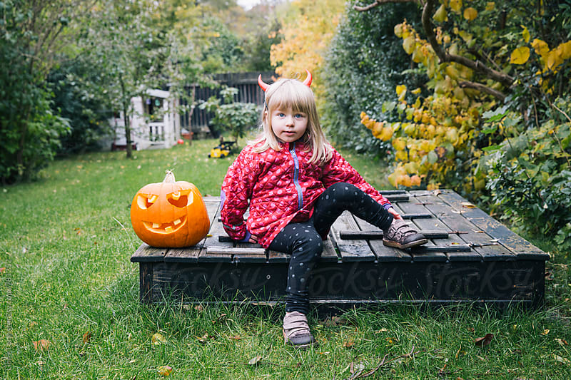 Little girl and pumpkin in autumn garden for Halloween by Lior + Lone for Stocksy United
