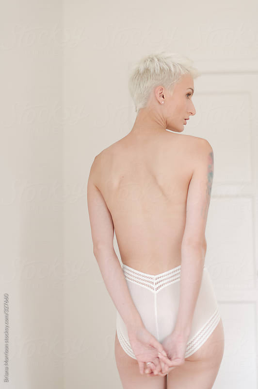 Young Blond Woman Wearing White Lingerie in a White Room by Briana Morrison for Stocksy United