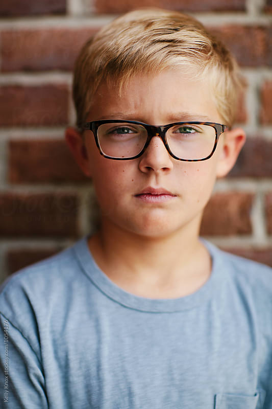 portrait of a serious blonde boy wearing glasses by Kelly Knox for Stocksy United
