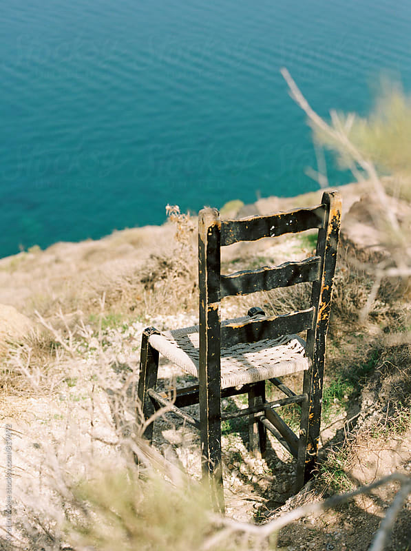 Chair on cliff in Santorini, Greece by Kirstin Mckee for Stocksy United
