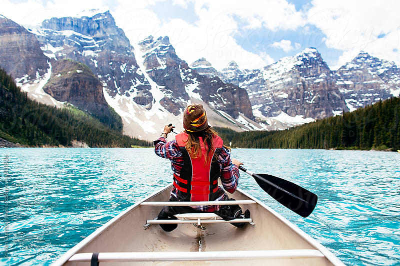 Back view of a woman canoeing in a vibrant blue lake with mountains in the background by Kristen Curette Hines for Stocksy United