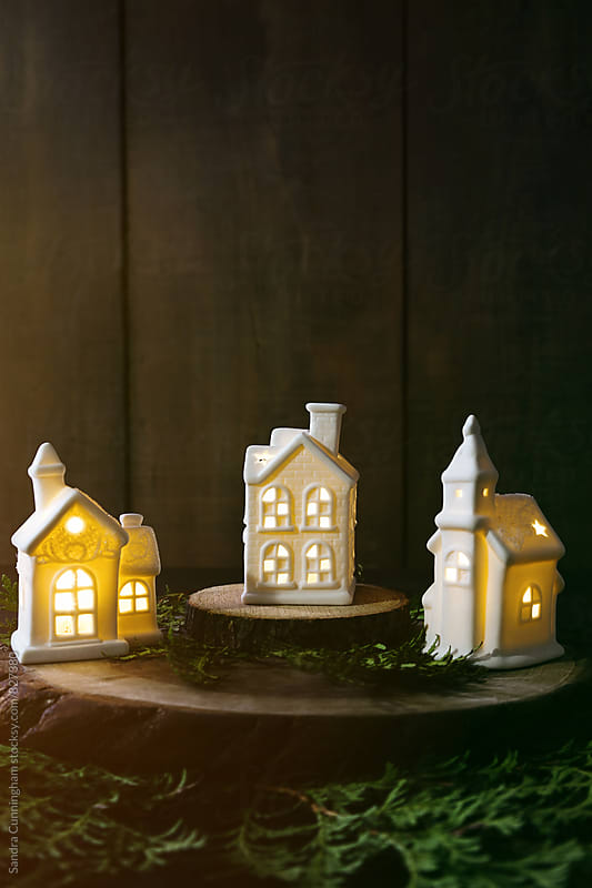 Small ceramic houses with lights and cedar branches by Sandra Cunningham for Stocksy United