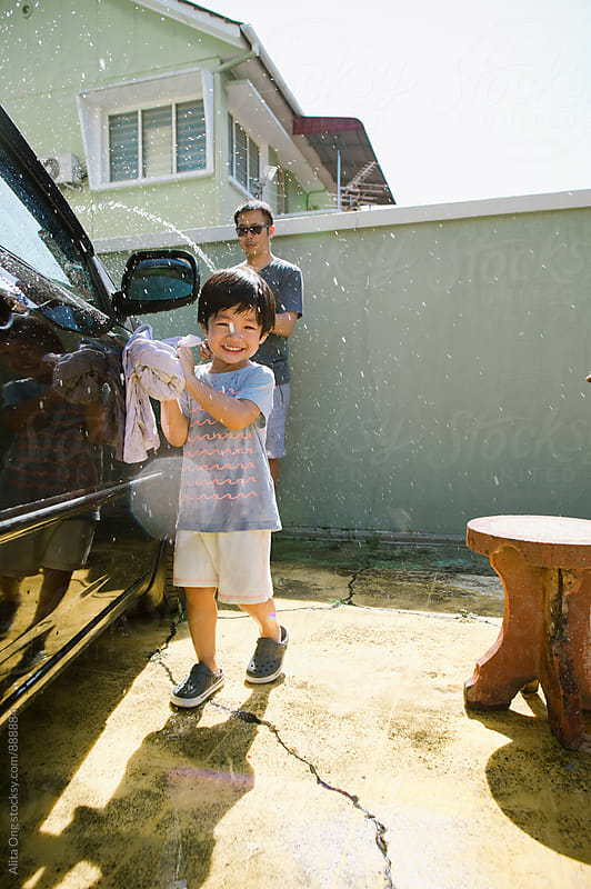 Joyful little boy washing car with dad by Alita Ong for Stocksy United