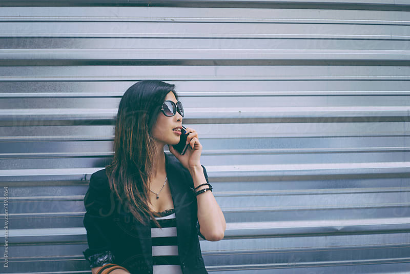 Chinese girl talking on the phone by Eva Plevier for Stocksy United