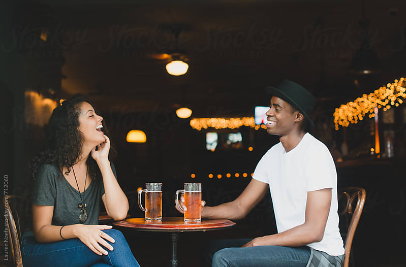 Cute couple drinking at a bar by Lauren Naefe for Stocksy United
