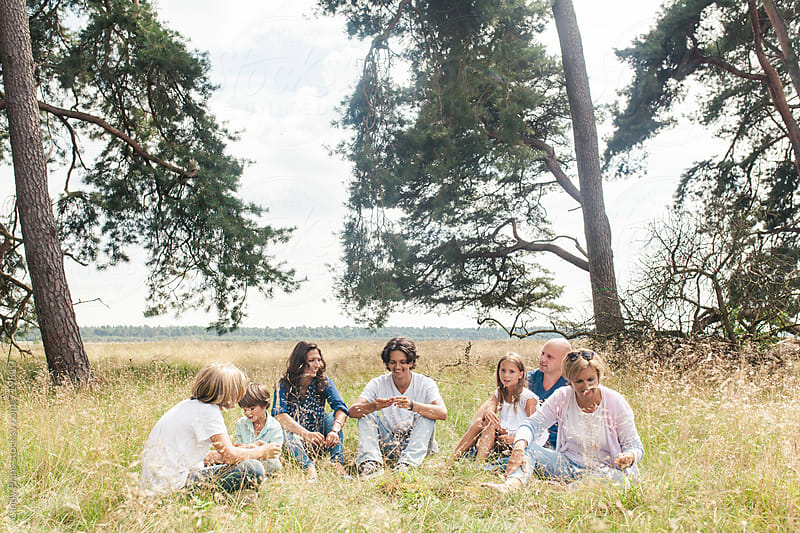 A family relaxing in a field under the trees in the summer by Cindy Prins for Stocksy United